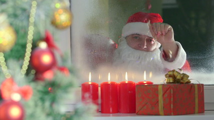Santa Claus knocking at window and looking at child
