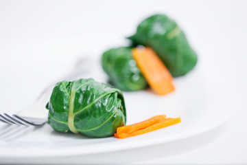 Chard rolls and carrot on plate