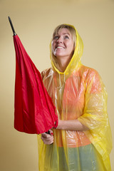 Woman in Poncho holding an umbrella about to rain