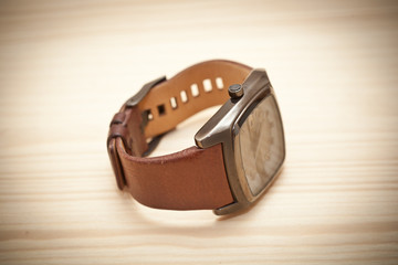 wristwatch on wooden surface