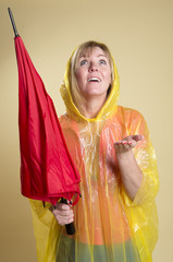 Woman in Poncho holding an umbrella expecting rain