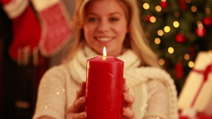 Pretty blonde holding candle at christmas
