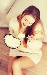 Happy caucasian woman is eating ice cream.