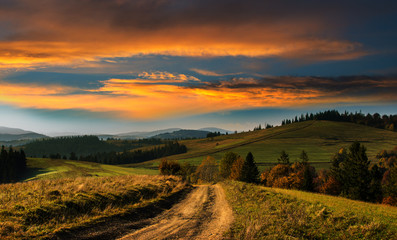 Wide road in the Carpathian Mountains at sunset.