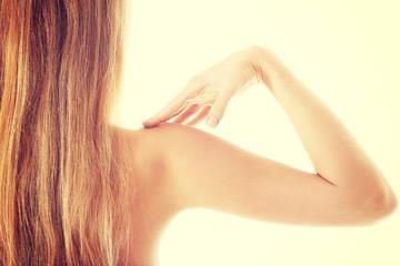 Beautiful caucasian topless woman toucing her shoulder,rear view