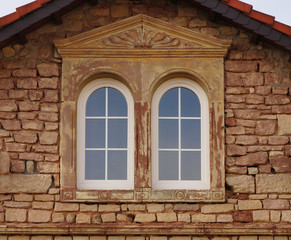 Buntsandsteinfassade mit PVC Bogenfenstern in Renovierung