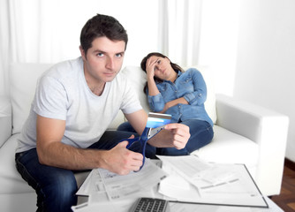 young husband cutting credit card with scissors woman depressed