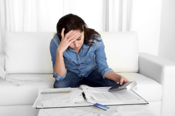 young woman worried at home in stress accounting with calculator