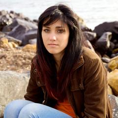 Cute girl sitting in front of ocean looking sad