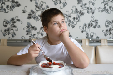 Boy teenager eating soup at  kitchen table