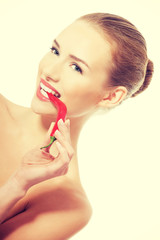 Beautiful caucasian topless woman with chili pepper in mouth.