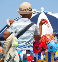 Peddler child sells balloons on the beach