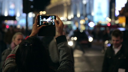 person taking picture with smartphone of piccadilly traffic