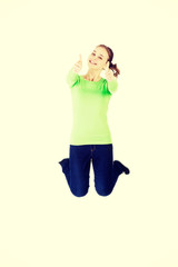 Woman jumping in the air with thumbs up
