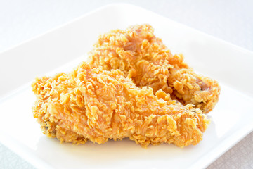 Fried chicken legs on a white plate