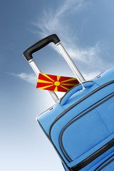 Destination Macedonia. Blue suitcase with flag.