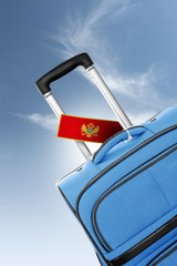 Destination Montenegro. Blue suitcase with flag.