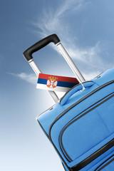 Destination Serbia. Blue suitcase with flag.