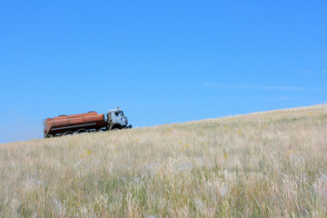 Gasoline tanker going on a steppe slope against a blue sky
