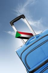 Destination Sudan. Blue suitcase with flag.