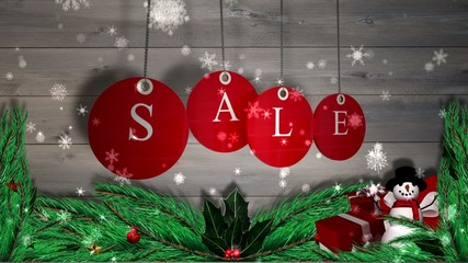 Red sale tags hanging against wood with festive decorations