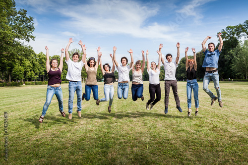 Group of ten teenagers jumping in the park in summer - 74255619