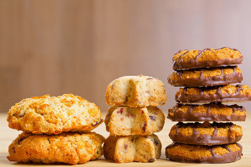 Different cookies in piles on wooden table
