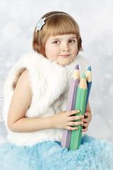 Beautiful girl wearing fur holding big crayons
