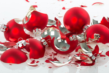 Red broken Christmas balls over a white background