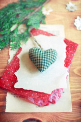 Soft Christmas heart on a piece of paper on wooden surface.