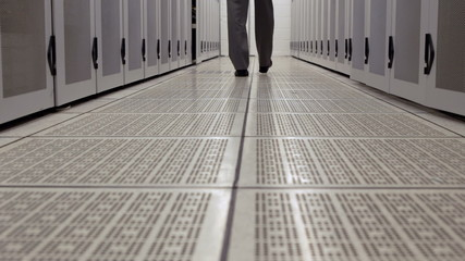 Data technician walking through locker hall