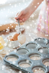 close up of woman filling muffins molds with dough