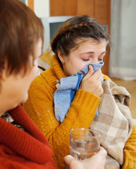 woman with blow nose uses handkerchief