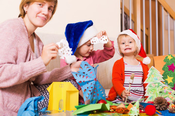 woman helping  daughters  to make decoration for Xmas