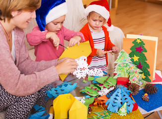 girls in Santa hats and smiling mom doing applique work