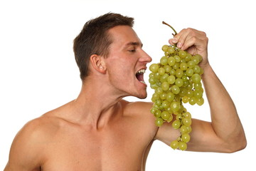 Athletic young man shirtless eats grapes on white background
