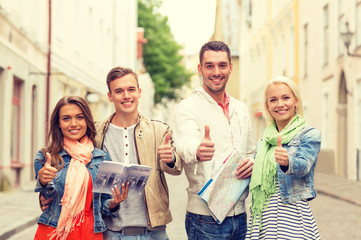 group of smiling friends with city guide and map