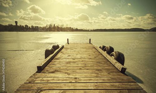 canvas print picture Vintage retro toned image of a pier on frozen lake.
