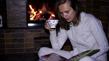 girl with cup of tea sitting near the fireplace