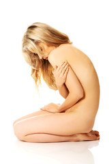 Side view of young nude woman sitting on knees