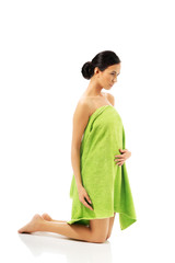 Full length woman kneeling wrapped in towel