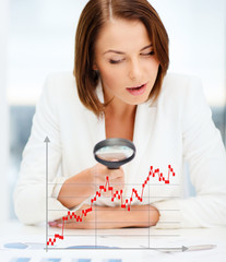 businesswoman looking through magnifier to graphs