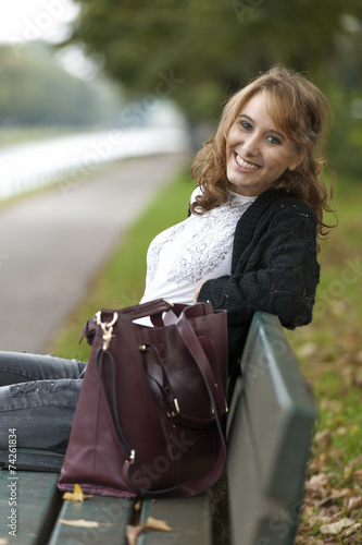 canvas print picture Freundliche Frau auf Parkbank