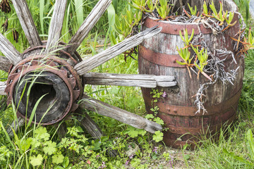 wheel of an old chariot and a barrel used for garden decoration