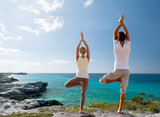 couple making yoga exercises on beach from back