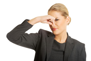 Woman pinching nose because of disgusting smell