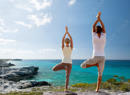 couple making yoga exercises on beach from back - 74262248
