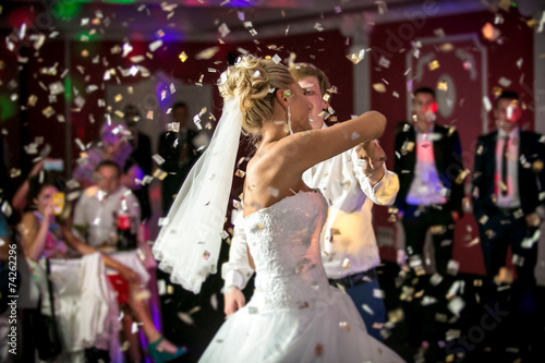 Leinwanddruck Bild blonde bride dancing at restaurant in flying confetti