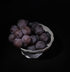 vase with grapes on a black background