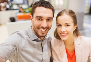 happy couple taking selfie in mall or office